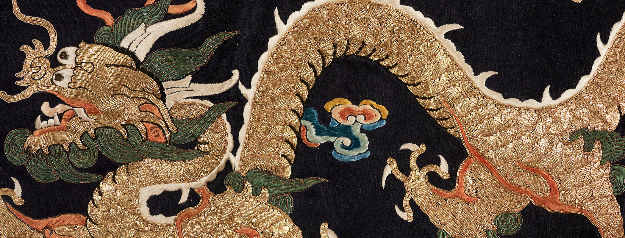a golden dragon embroidered on a black background